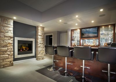 Basement bar with custom cabinetry and stone fireplace