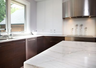 Modern kitchen with quartzite countertops and white and wood custom cabinets