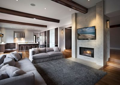 Modern new build family room with marble fireplace and wood beams