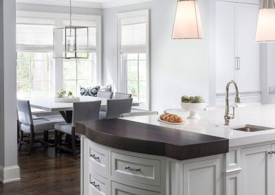 Traditional kitchen with butcher block island and white cabinets