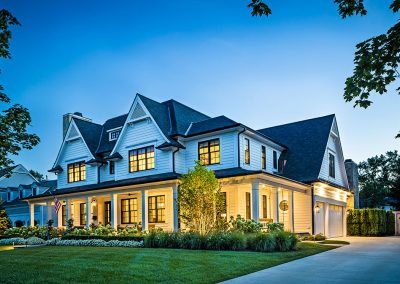 White modern farmhouse with carriage garage doors and Bevolo gas lantern