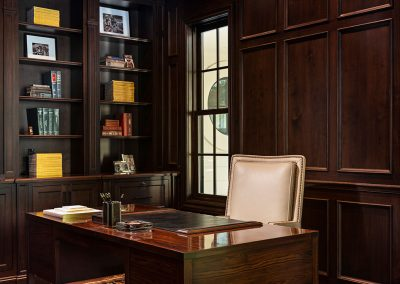 Library with built-in book shelf and raised paneled walls