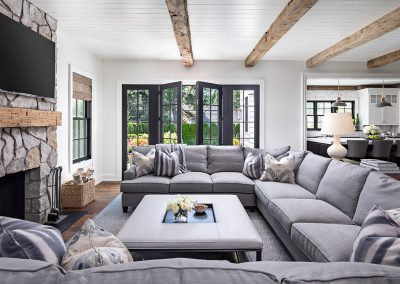 Modern farmhouse family room with barn beams and stone fireplace