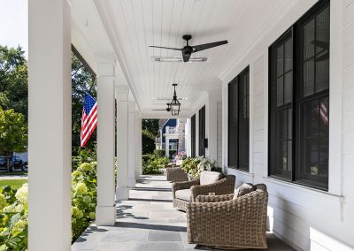 Front porch of modern farmhouse with infrared heaters and blue stone