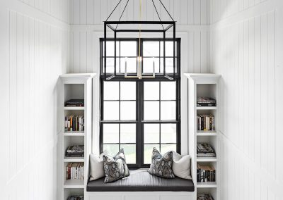 Stairway with built-in bookshelf and window seat and shiplap
