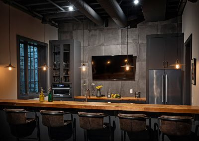 Lower level bar with wood countertops and grey custom cabinets