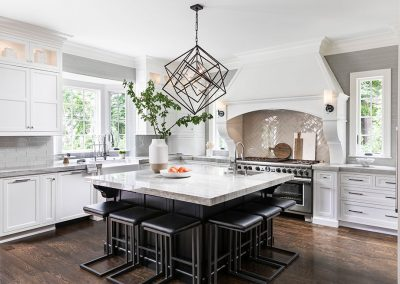 Transitional white kitchen with custom wood hood and sconces on hood