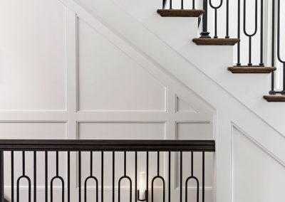 Transitional foyer staircase with raised paneling and iron spindle stair